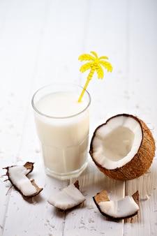 Glas kokosmelk op witte houten lijst. selectieve aandacht