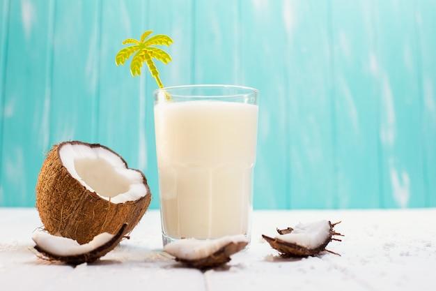 Glas kokosmelk op witte houten lijst