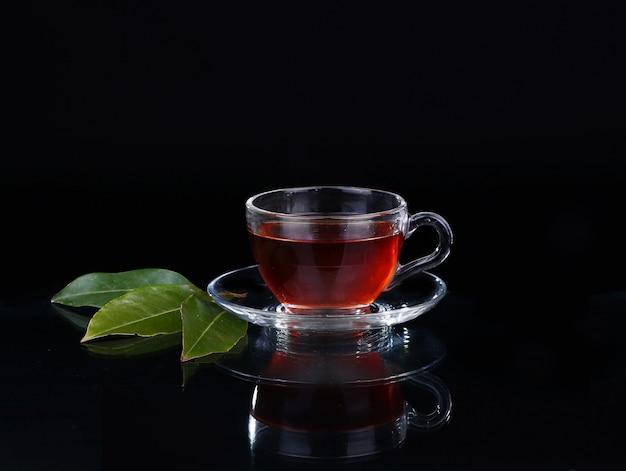 Glas kopje thee op zwart.