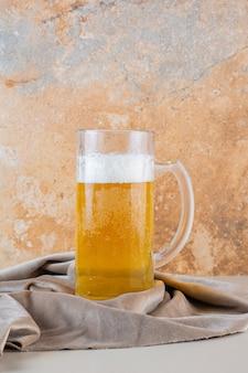 Glas koud gouden bier dat op een licht tafelkleed wordt geïsoleerd
