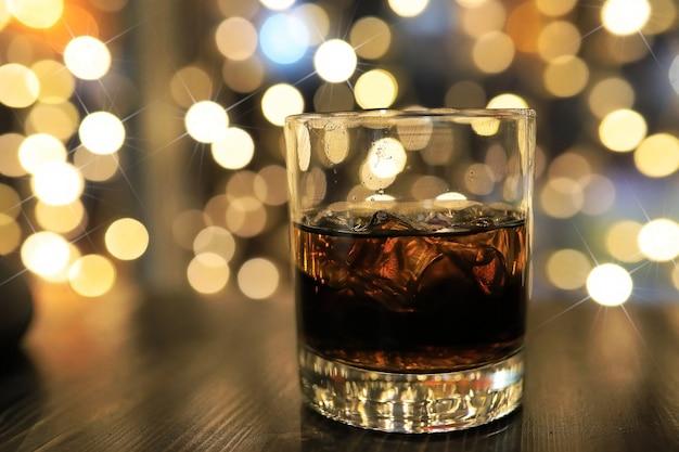 Glas koude alcoholische drank met ijs op tafel