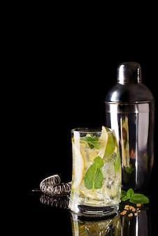 Glas koude cocktaildrank met tonic geserveerd met bruine suiker en shaker