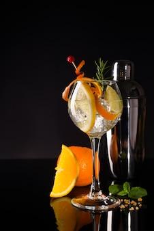 Glas koude cocktaildrank met witte wijn geserveerd met bruine suiker, sinaasappel en shaker