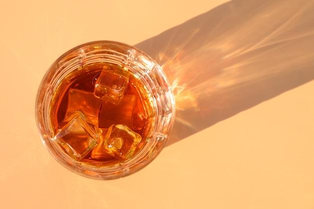 Glas koude whisky op beige met zonnige schaduw.