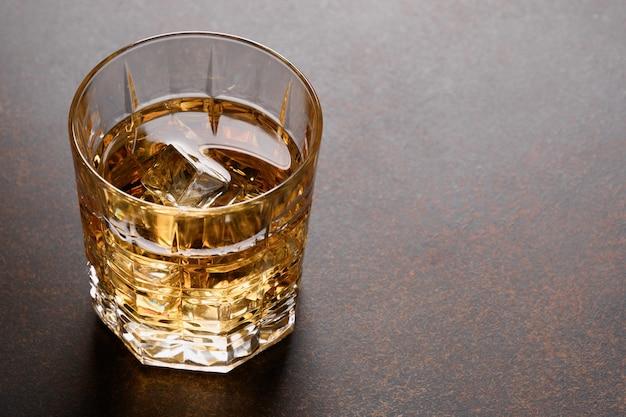 Glas koude whisky op donkere achtergrond. detailopname.
