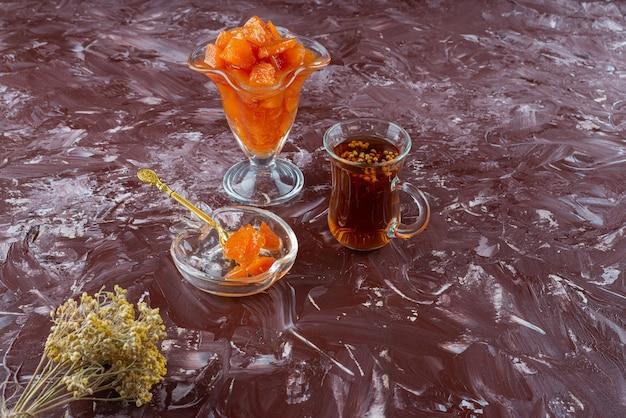 Glas kweepeerjam en glas zwarte thee op tafel.