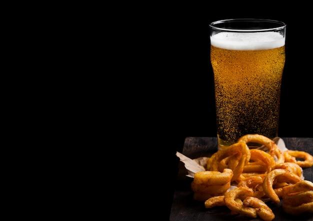Glas lager bier met krullende frietjes snacks op vintage houten bord