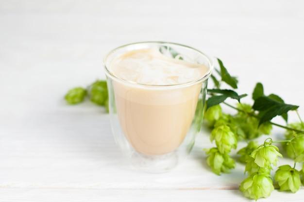 Glas latte met een takje hop op wit