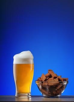 Glas licht bier met schuim en plaat van crackers op blauw