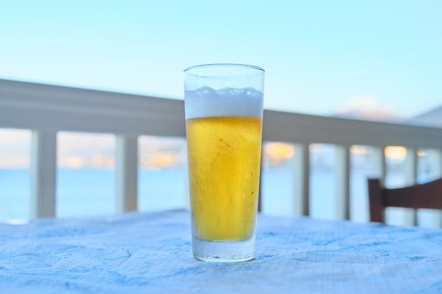 Glas licht bier op tafel in het café van het resort