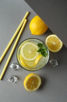 Glas limonade en ingrediënten op lichtgrijze achtergrond