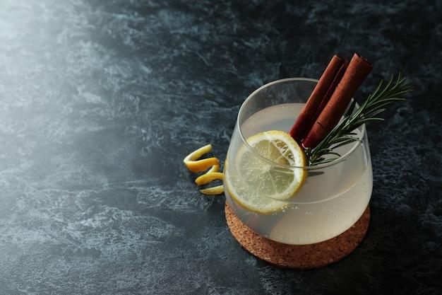 Glas limonade met kaneel en rozemarijn op zwarte smokey tafel
