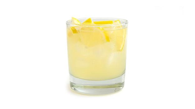 Glas limonade met stukjes citroen en ijs. zijaanzicht.