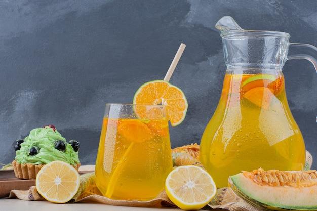 Glas limonades met schijfjes citroen op blauw.