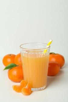 Glas mandarijnensap en ingrediënten op witte achtergrond