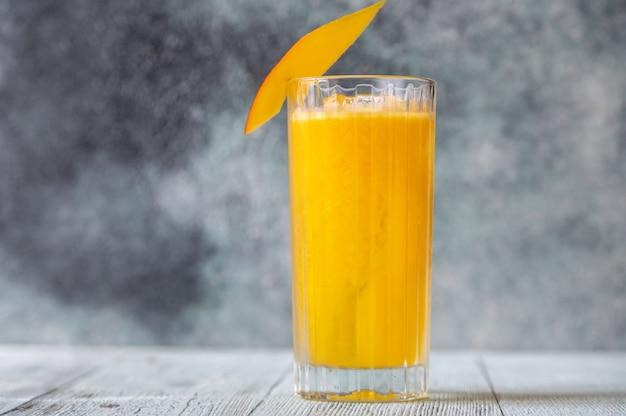 Glas mango rum cooler cocktail gegarneerd met plakje verse mango