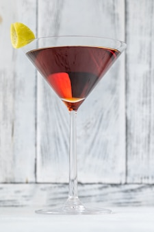 Glas martinez-cocktail gegarneerd met citroenschil