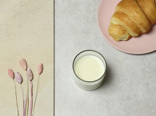 Glas melk, cake en boeket bloemen op granieten textuur