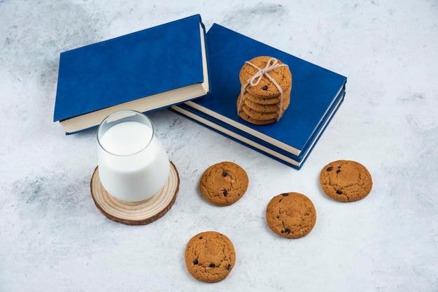 Glas melk, chocoladeschilferkoekjes en boek op marmeren oppervlak.