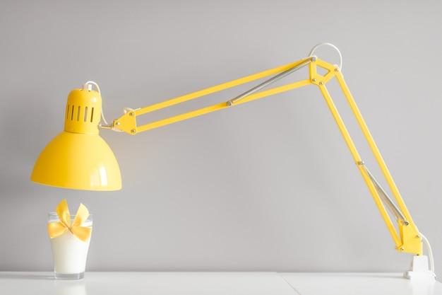 Glas melk die met gele bowtie wordt verfraaid die zich op lijst onder gele lamp bevinden