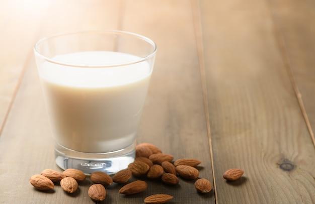 Glas melk en amandelennoten op houten achtergrond,
