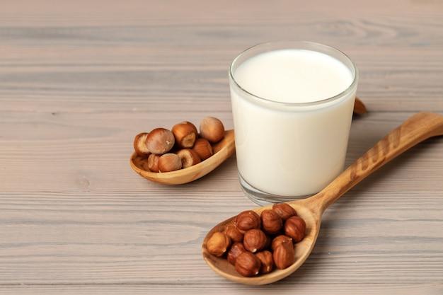 Glas melk en hazelnoten op houten tafel