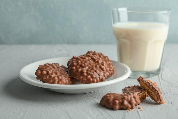 Glas melk en plaat met chocoladekoekjes op grijze lijst tegen lichte achtergrond