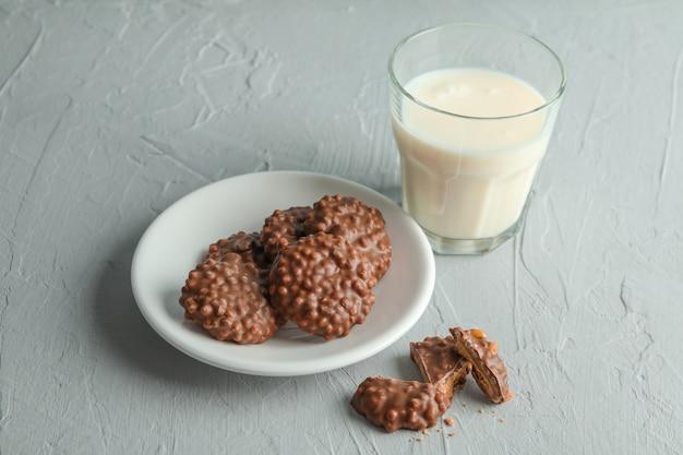 Glas melk en plaat met chocoladekoekjes op grijze tafel,