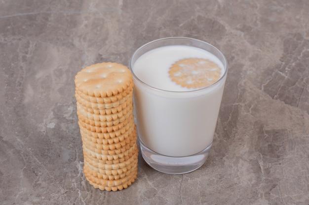 Glas melk en stapel koekjes marmeren tafel.