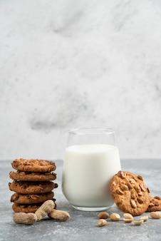 Glas melk en stapel koekjes met honing op marmeren tafel.