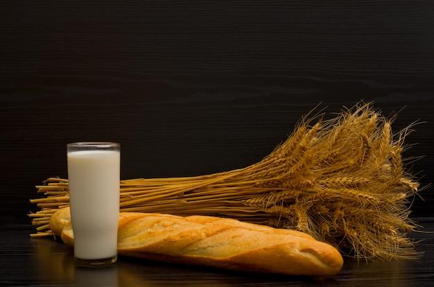 Glas melk en vers brood en een schoof op een zwarte achtergrond