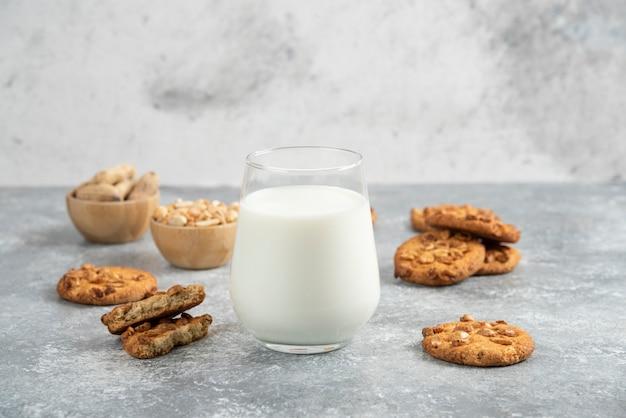 Glas melk en zelfgemaakte koekjes met honing op marmeren tafel.