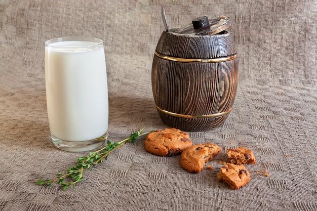 Glas melk, koekjes, tijm en hout van honing op tafel