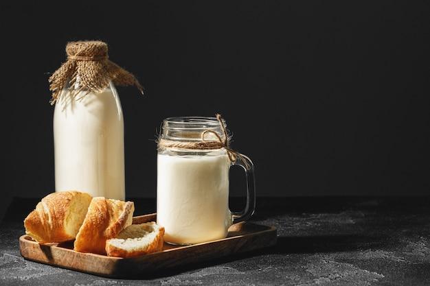 Glas melk met gesneden stokbrood op houten bord