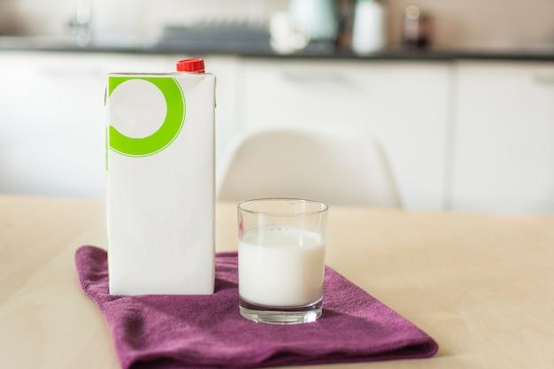 Glas melk met servet en papieren fles op houten tafel meer dan vervagen witte keuken