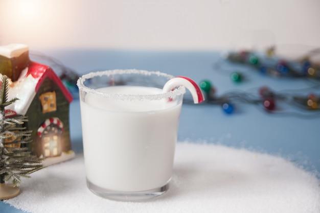 Glas melk, snoepgoed, huis en kerstboomminiaturen op blauw