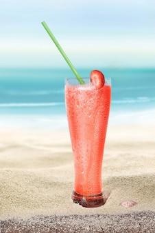 Glas met aardbeiensap op het strandzand