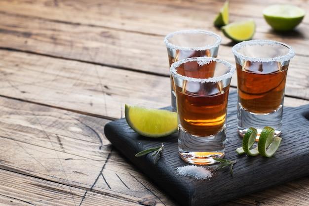 Glas met alcohol, zout en limoen op een houten tafel