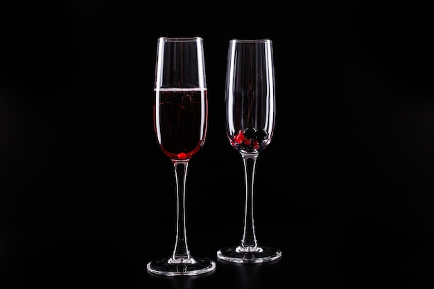 Glas met bessen en rode champagne alcohol cocktail staat op een zwarte achtergrond
