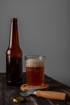 Glas met bier en een flesje bier op een donkere tafel