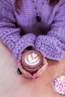 Glas met cacao. langharig meisje dat haar handpalmen opwarmt met een groot glas cacao terwijl ze lichtroze nagels heeft