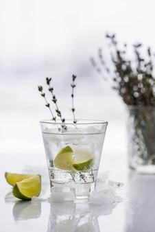 Glas met cocktail met limoen, tijm en ijs