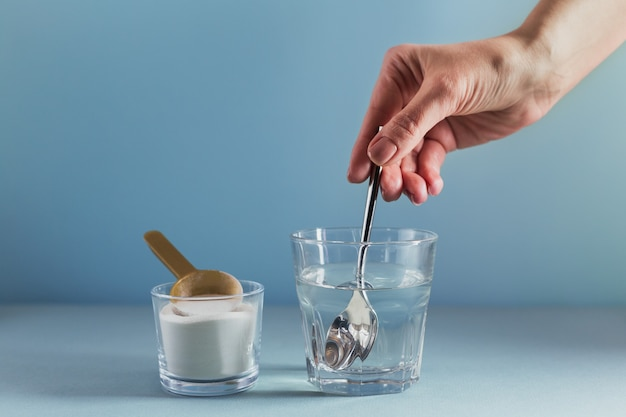 Glas met collageen opgelost in water en collageen proteïnepoeder op lichtblauw oppervlak. de hand van de vrouw houdt een lepel. gezond levensstijlconcept.