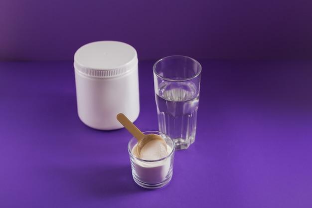 Glas met collageen opgelost in water en collageenproteïnepoeder op paarse tafel