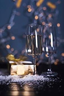 Glas met drankje aan boord in de buurt van ornament sneeuw en huidige doos
