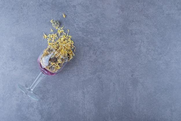 Glas met droge kruiden op grijs.