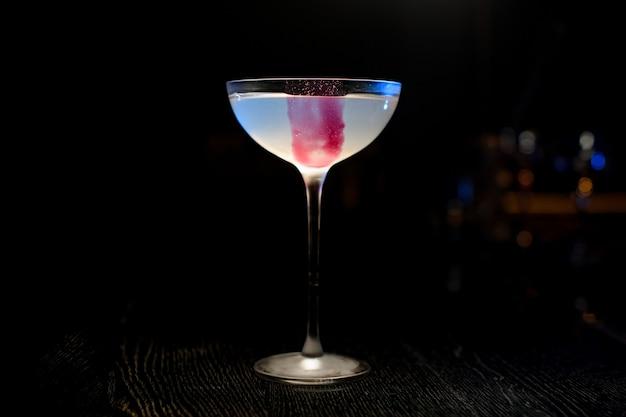 Glas met een roze ijsblokje en een lichtblauwe cocktail die zich in de bar bevindt