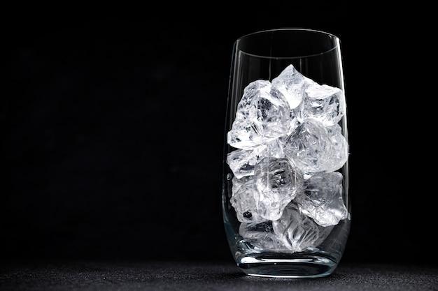 Glas met gemalen ijs op zwarte achtergrond