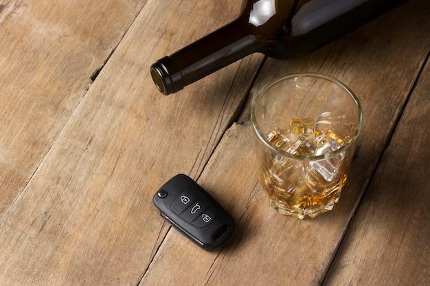 Glas met gemorste alcoholische drank en autosleutels op een houten achtergrond. dronken rijden concept, stoppen met drinken en rijden.