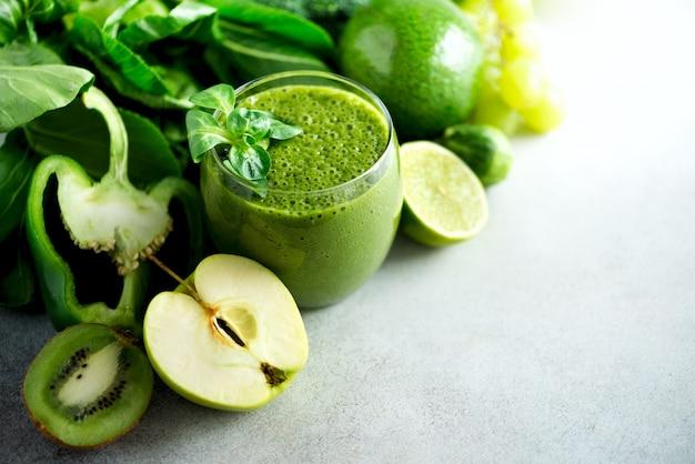 Glas met groene gezondheids-smoothie, boerenkoolbladeren, limoen, appel, kiwi, druiven, banaan, avocado, sla. ruw, veganistisch, vegetarisch, alkalisch voedselconcept.